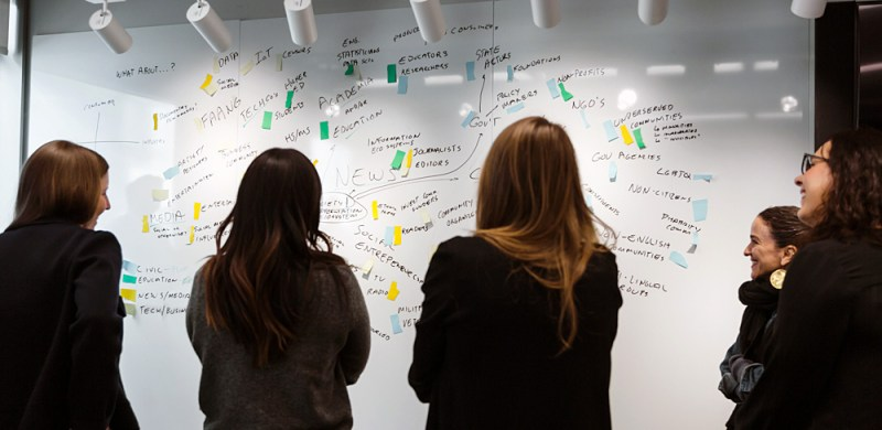 Members of one of the small groups review their systems map work. (Photo: (Photo: Jo Chiang / NYC Media Lab)